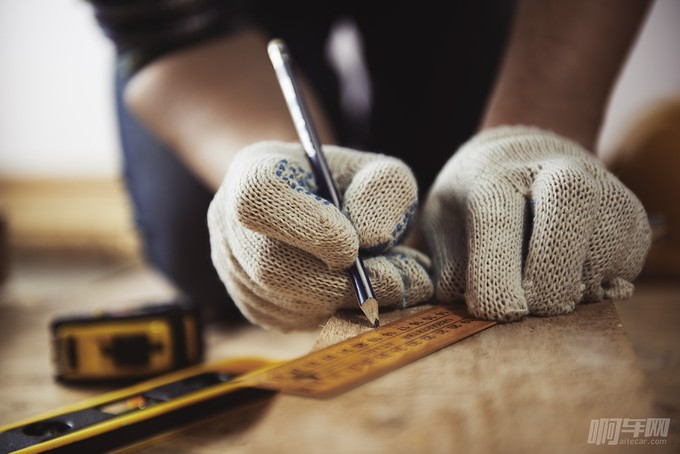 Close-up of craftsman hands in protective gloves measuring woode